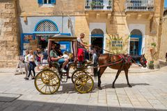 Tourists being toured by horse carriage around the old city streets of Mdina, Malta. MDINA, MALTA - MAY 01, 2018: Tourists being toured by horse carriage around Stock Photo