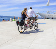 Tourists on a bicycle tandem ride along the waterfront. Stock Images