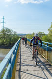 Tourists bicycles bridge. Ivano-Frankivsk, Ukraine - May 3, 2015: tourists on bicycles riding through a pedestrian bridge over the river Bistrica. Bridge railing Royalty Free Stock Photography