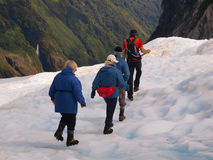 Group of tourists following a guide on a glacier Royalty Free Stock Photography