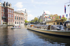 Tourists board canal boat in centre of amsterdam Stock Photos