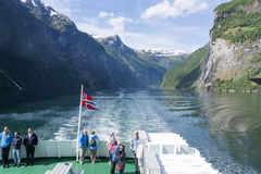 Tourists on board the cruise ship admire spectacular views of the fjord on June 29, 2016 in Geirangerfjord, Norway. Royalty Free Stock Photo