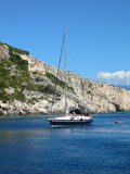 Tourists on board yacht. Blue yacht full of tourists sunbathing, anchored by the coastline of the Greek island Zante in the Ionian sea Stock Images