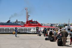 Tourists boarding Hellenic Seaway Ferry. Athens, Greece - May 27, 2013: Tourists and tour guide are waiting for boarding Hellenic Seaway ferry at Piraeus Port in Royalty Free Stock Photos