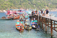 tourists boarding to the fishing boat and long tail boat. Royalty Free Stock Photography