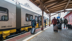 Tourists boarding the train. Tourists with wheeled luggage cases boarding ready to depart local train operated by Koleje Dolnoslaskie company standing on a Royalty Free Stock Images