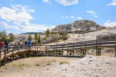 YELLOWSTONE NATIONAL PARK, WYOMING, USA - JULY 17, 2017: Tourists on boardwalk at Palette Spring area, Mammoth Hot Springs Terrace Royalty Free Stock Photography