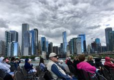 Tourists on boat as storm clouds gather above downtown Chicago. Storm clouds swirl above downtown Chicago, Illinois. Blue and gray buildings are lit up. Tourists royalty free stock photo