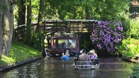 Tourists in a boat on the canal of the village of Giethoorn. Tourists in boats and kayaks on the canal of the famous village of Giethoorn in Overijssel, The stock video footage