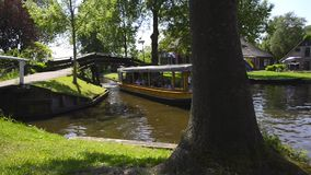 Tourists in a boat on the canal of the village of Giethoorn. Tourists in a tour boat on the canal of the famous village of Giethoorn in Overijssel, The stock footage