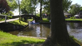Tourists in a boat on the canal of the village of Giethoorn. Tourists in a tour boat on the canal of the famous village of Giethoorn in Overijssel, The stock video