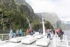 Tourists on boat cruises in the fjord of Milford Sound, South island of New Zealand Royalty Free Stock Photos