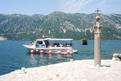 Tourists on a boat docking on the island of Lady of the rock Stock Image
