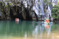 Tourists on boat at the entrance of the Underground River, one of the new Seven Wonders of the nature. Puerto Princesa, The Philippines - January 11,2015 Stock Photography