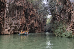 Tourists on a boat in the river in the Jiuxiang scenic area in Yunnan in China. Thee Jiuxiang caves area is near the Stone Forest Royalty Free Stock Images