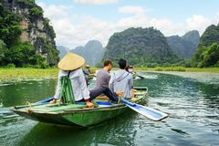 Tourists in boat. Rower using her feet to propel oars, Vietnam. Tourists traveling in boat along the Ngo Dong River at the Tam Coc portion, Ninh Binh Province Stock Image