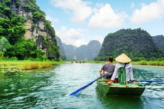 Tourists in boat. Rower using her feet to propel oars. Vietnam. Tourists traveling in boat along the Ngo Dong River at the Tam Coc portion, Ninh Binh Province Royalty Free Stock Images