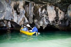 Tourists in boat swim into the cave of the island. Royalty Free Stock Photos
