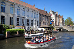 Tourists boat trip on the Dijver Canal, Bruges. Tourists enjoy a boat sightseeing tour on the Dijver Canal outside of the Hotel de Orangeries, Bruges old town Royalty Free Stock Image