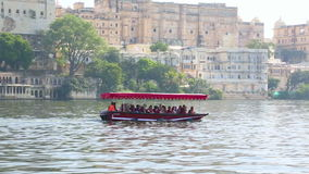 Tourists boat. UDAIPUR, INDIA - November 23, 2012: Unidentified tourists take boat ride in front of City Palace on February 8, 2011 in Udaipur, India stock video