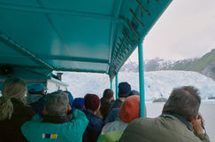 Tourists in boat watching glacier. Tourists watching melting glacier from tour boat, Alaska, USA Stock Photo