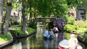 Tourists in boats on the canal of the village of Giethoorn. Tourists in boats on the canal of the famous village of Giethoorn in Overijssel, The Netherlands on a stock video