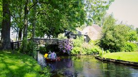 Tourists in boats on the canal of the village of Giethoorn stock video footage