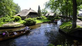 Tourists in boats on the canal of the village of Giethoorn. Tourists in boats on the canal of the famous village of Giethoorn in Overijssel, The Netherlands on a stock video footage