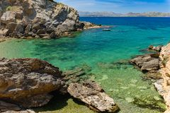 Tourists on boats enjoying a sunny day on a rocky bay in Mallorc. A, on the seaside coast in the Victoria peninsula next to the city of Alcudia Royalty Free Stock Images