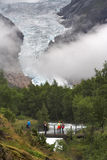 Tourists on the bridge over the stream at Briksdal glacier Royalty Free Stock Photography