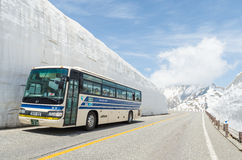Tourists bus move along the japan alps snow wall at tateyama kurobe alpine route Royalty Free Stock Images