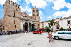 Tourists and bus on square of Duomo in Monreale. MONREALE, ITALY - JUNE 25, 2011: tourists and bus on square of Duomo di Monreale town in Sicily. The cathedral stock photo