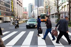 Tourists and business people crossing the street at Shinjuku. Tokyo, Japan - April 12, 2014 : Tourists and business people crossing the street at  Shinjuku Stock Photos