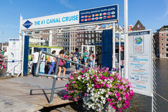 Tourists buying tickets at departure place of Amsterdam canal cruises Royalty Free Stock Image