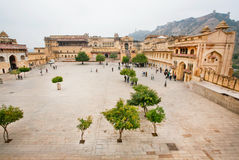 Tourists came to the courtyard with trees and historical structures of Amber Fort Royalty Free Stock Images