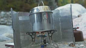 Tourists camp near the river. Installation camp stove burner. Propane fuel, camp matches, windshield camping stove