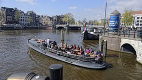Tourists on canal, Amsterdam, Holland royalty free stock photos