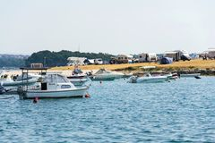 Tourists, caravans and boats on Kamenjak peninsula by the Adriatic sea in Premantura, Croatia. royalty free stock photos
