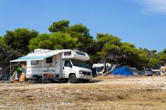 Tourists, caravans and boats on Kamenjak peninsula by the Adriatic sea in Premantura, Croatia. royalty free stock photography
