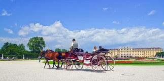 Tourists on a carriage in Vienna. Image coach with tourists in the background of an ancient castle in Vienna, Austria Royalty Free Stock Image