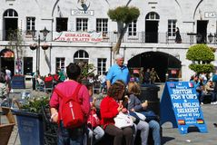 Tourists in Casemates Square, Gibraltar. Tourists sitting on a bench eating ice creams in Grand Casemates Square, Gibraltar, United Kingdom, Western Europe Royalty Free Stock Image