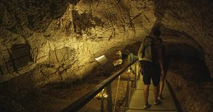 Tourists in cave museum. NATIONAL PARK KRKA, CROATIA - August 16, 2014: Tourists take a tour of the Prehistoric cave museum above Roski waterfall, where they stock footage