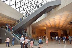 Tourists in the central hall under the Louvres pyramid in Paris. PARIS, FRANCE -23 may 2018 :  tourists in the central hall, inside the Louvres pyramid before royalty free stock photos