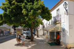 Tourists check map in the shadow on a hot day at the street in Lagos, Portugal. Royalty Free Stock Photography