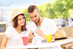 Tourists checking pictures in a cafe Royalty Free Stock Photos