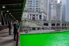 Tourists and Chicagoans gather to observe the dyed-green Chicago River. In celebration of St. Patty`s Day royalty free stock photo