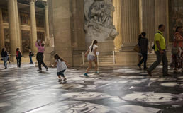 Tourists and children enjoy JR faces on floor of Pantheon in Paris Royalty Free Stock Photography