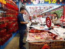 Tourists choose from a variety of souvenir products at a store or shop in Chinatown, Singapore. Stock Photo
