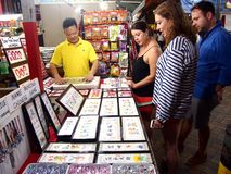 Tourists choose from a variety of souvenir products at a store or shop in Chinatown, Singapore. Royalty Free Stock Photography
