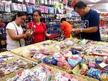 Tourists choose from a variety of souvenir products at a store or shop in Chinatown, Singapore. Stock Image